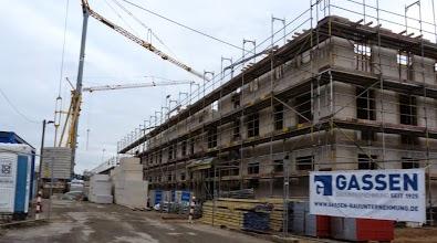 Baustelle: Wohnblock mit Gerüst und Dixieklo.