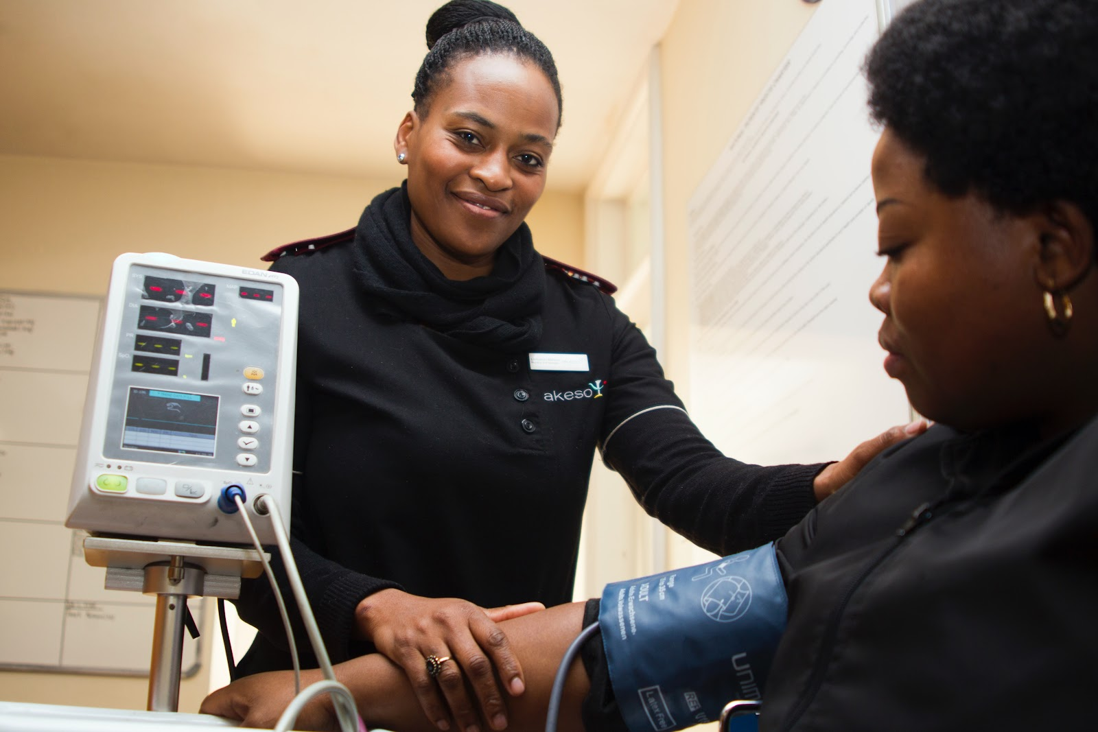 A smiling nurse who has applied a blood pressure cuff onto a seated woman's arm looks into the camera as the machine takes a reading.