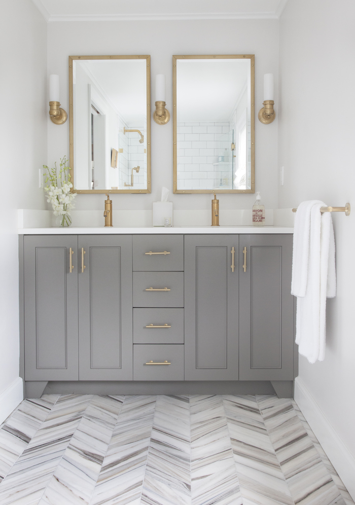 grey bathroom vanity with white countertop, brass hardware and herringbone tile flooring
