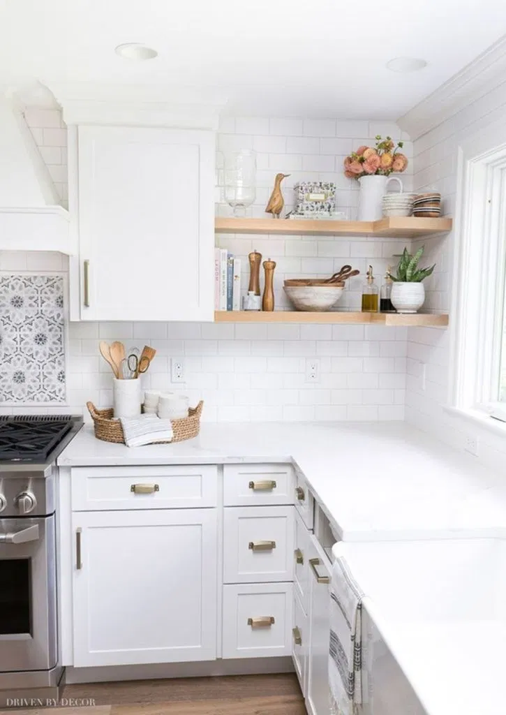 kitchen with white shaker cabinets and cool brass cabinet hardware. bright white countertops and white subway tile backsplash are accentuated by a window casting natural light
