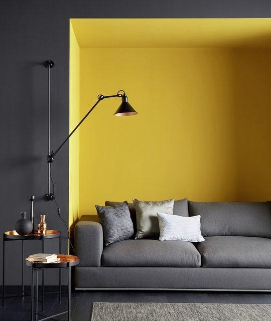 Sala com móveis, piso e parede principal na cor cinza e parede de fundo amarela