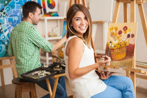 a woman enjoying herself while painting a canvas on an easel