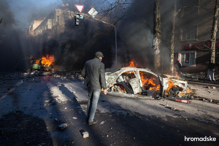 Мужчина смотрит на автомобили, сожженные во время столкновений между протестующими и силовиками на пересечении улиц Институтской и Шелковичной в Киеве, 18 февраля 2014 года