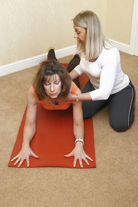 mujer ayudando a otra a hacer la Postura de Media Cobra o Ardha Bhujangasana