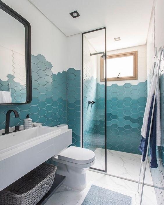 Banheiro com azulejo hexagonal meia parede por todo banheiro em degrade de tons de azul, piso porcelanato branco, bancada da pia branca com torneira preta e espelho e box de vidro com moldura preta