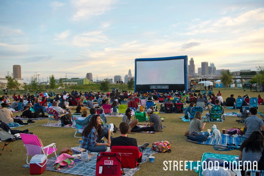 People gather at an LA park in front of a movie screen