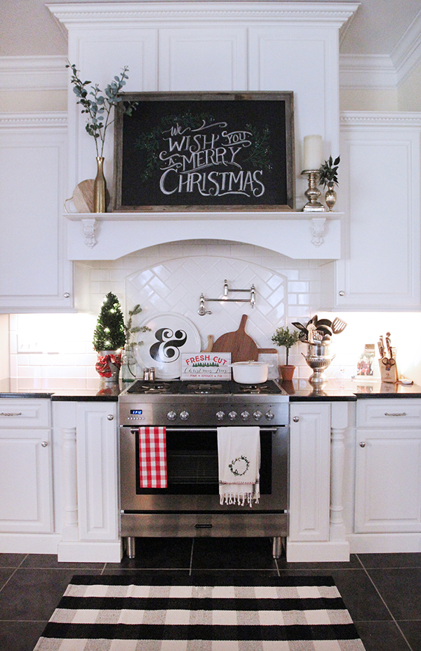 farmhouse kitchen with large chalkboard christmas sign hanging on the range hood. a mini christmas tree and more holiday signs are displayed above the stove