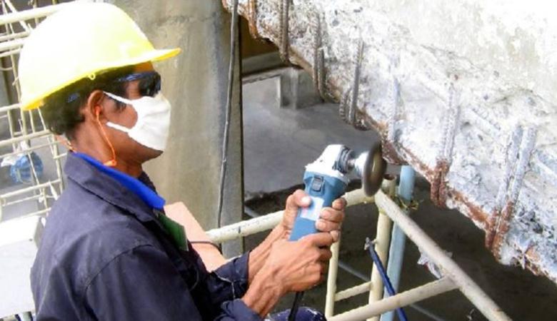 Operário usa cortador elétrico para cortar armação metálica corroída.