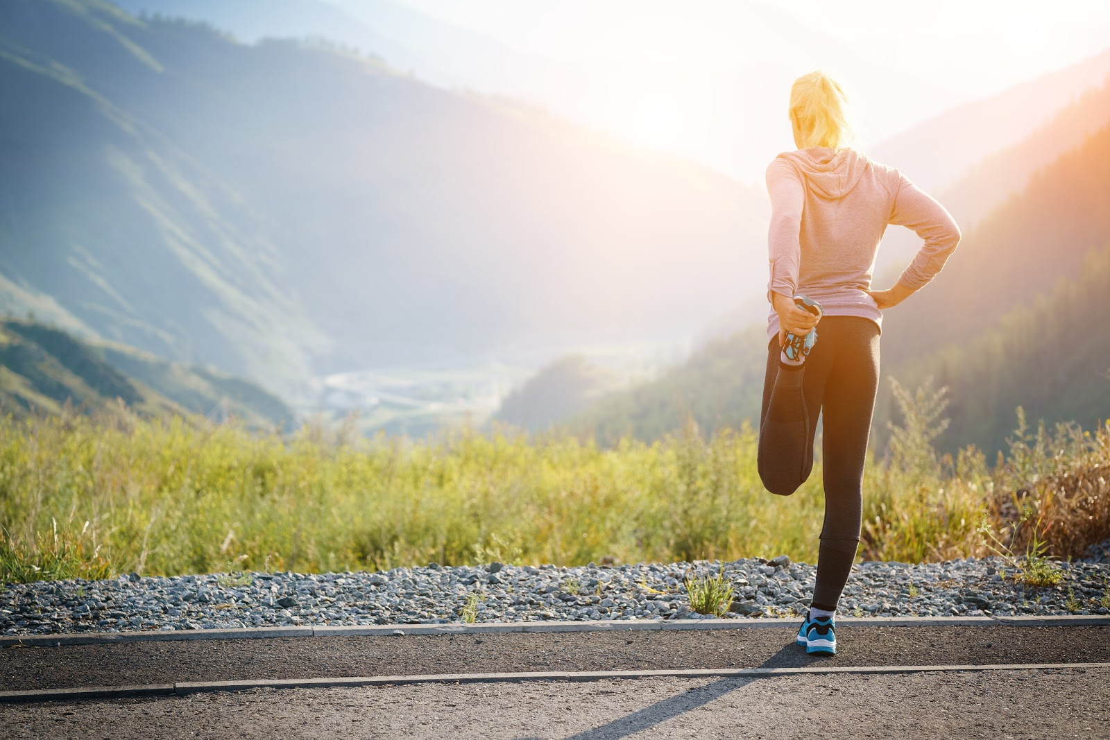 A woman on an open road with mountain scenery, preparing to exercise