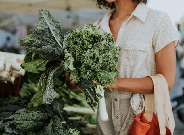 woman holding a bundle of two different types of kale
