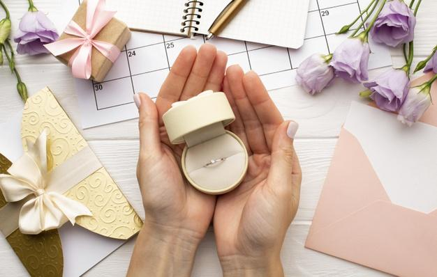 Feminine hands holding wedding ring Free Photo