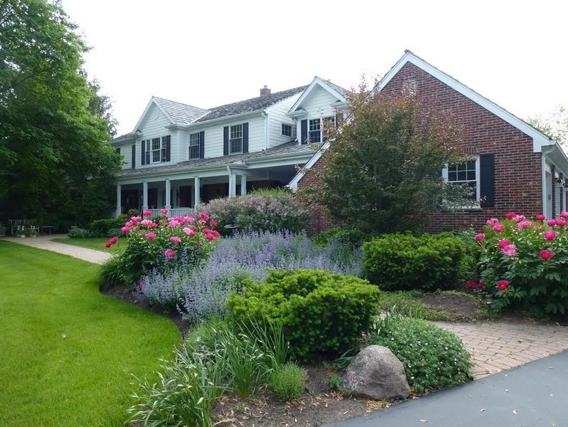 Home with shutters and luscious landscaping