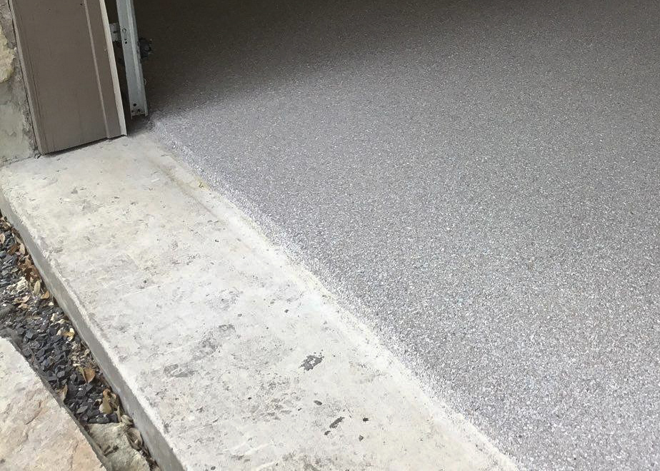 A close up of a garage floor near the garage door opening with a grey colored coating that stops right before the door.