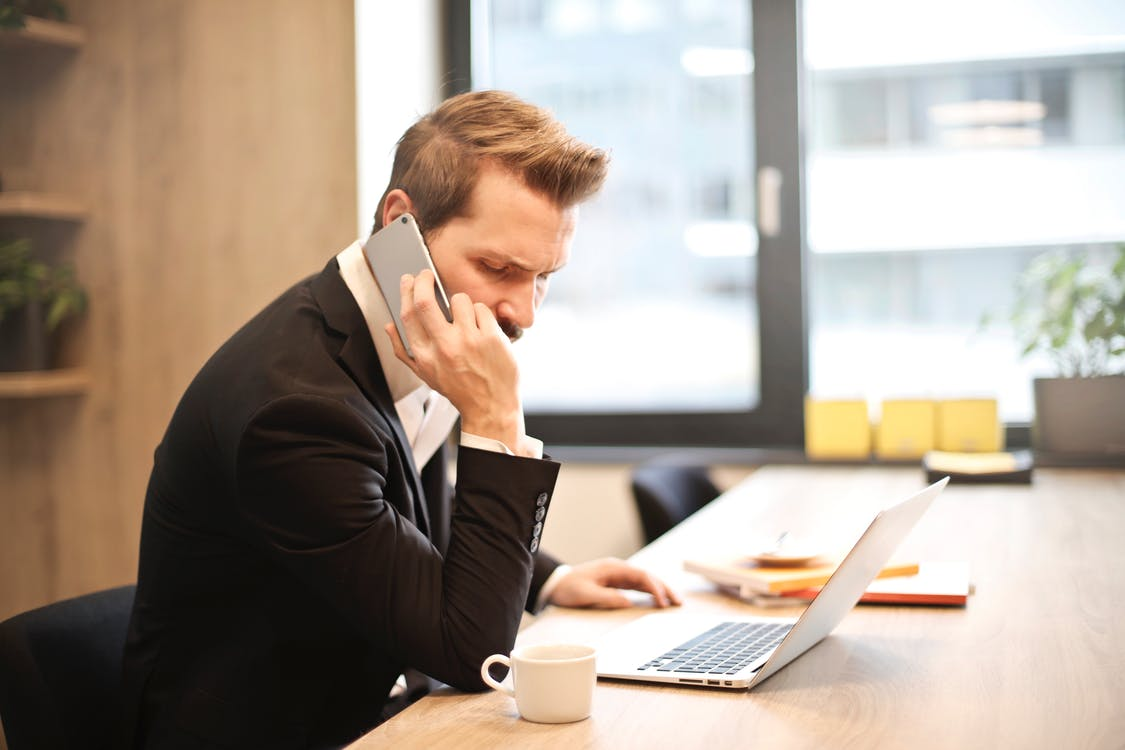 using emergency business contacts list man-having-a-phone-call-in-front-of-a-laptop