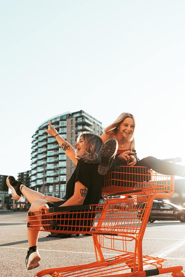 Duas amigas sentadas em um carrinho de compras e rindo