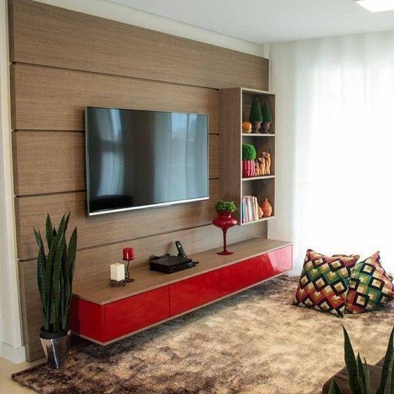Sala com painel marrom com detalhe vermelho, enfeites vermelhos, plantas e tapete marrom.