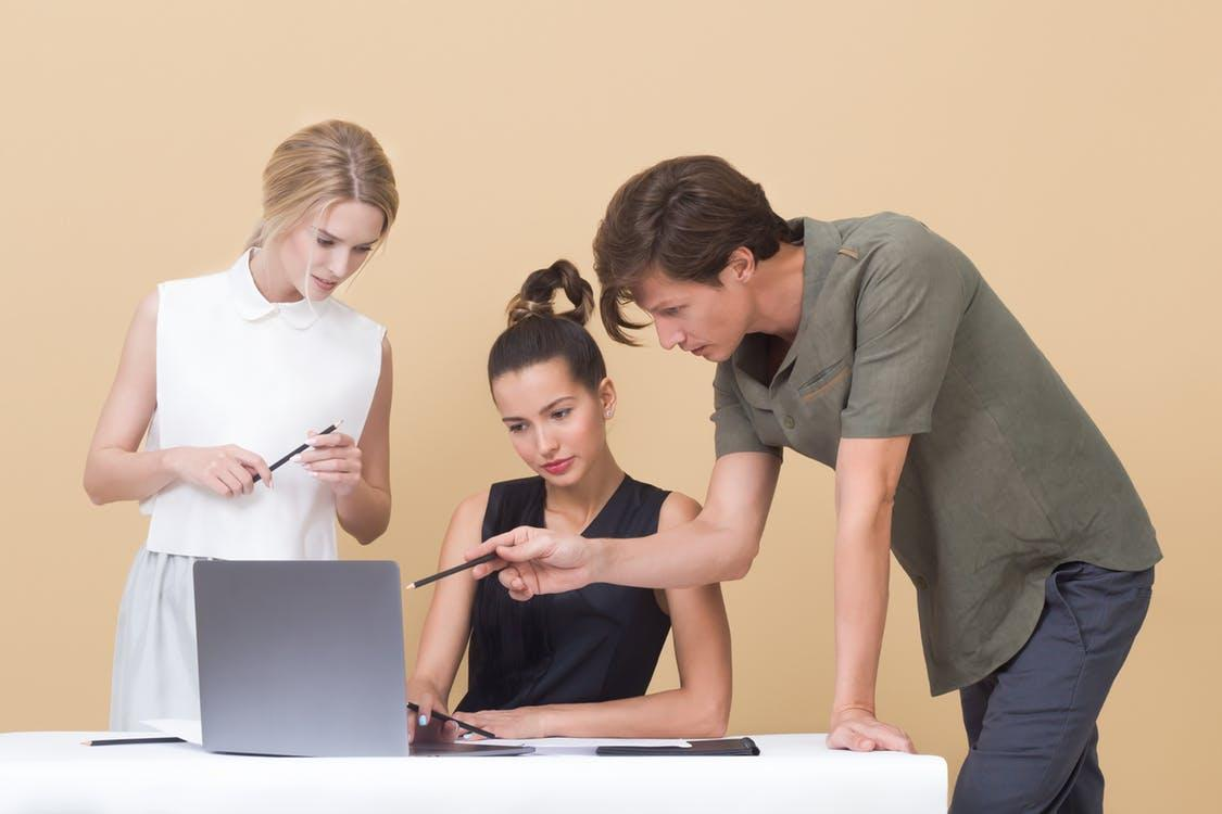 Two Woman and One Man Looking at the Laptop - logo