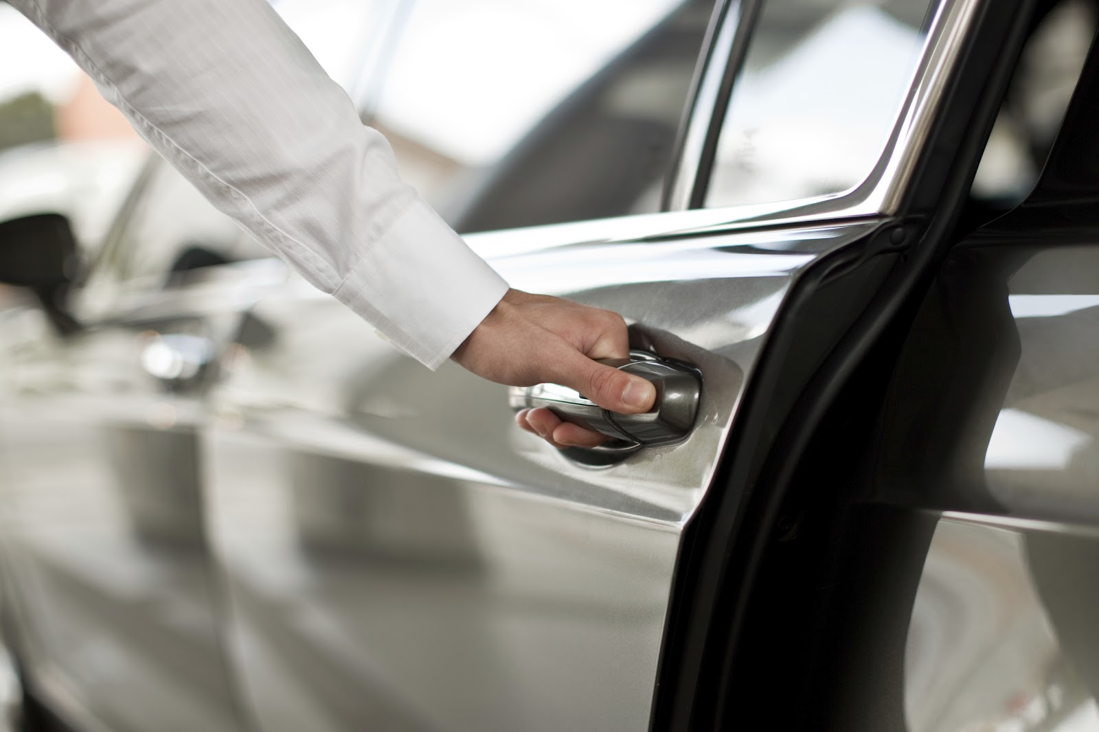 Pulling the handle of the rear driver-side door on a passenger vehicle.