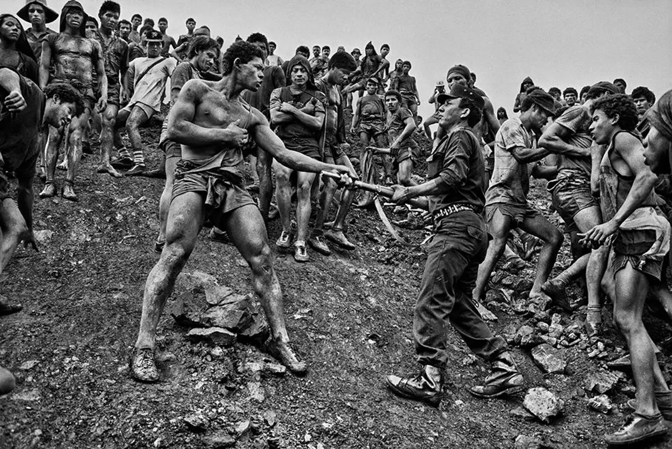 A black and white image of two men who appear to be arguing, by famous photographer Sebastião Salgado