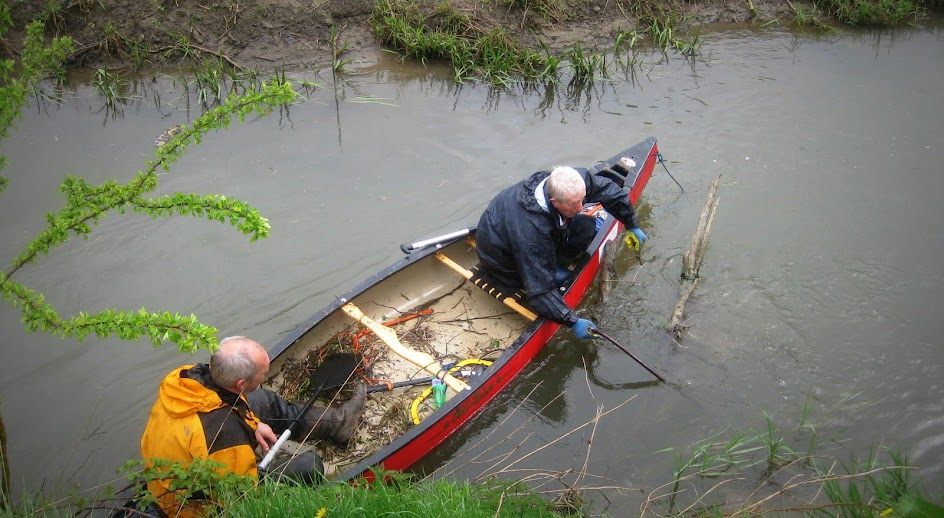 Volunteers in canoes clear the small river