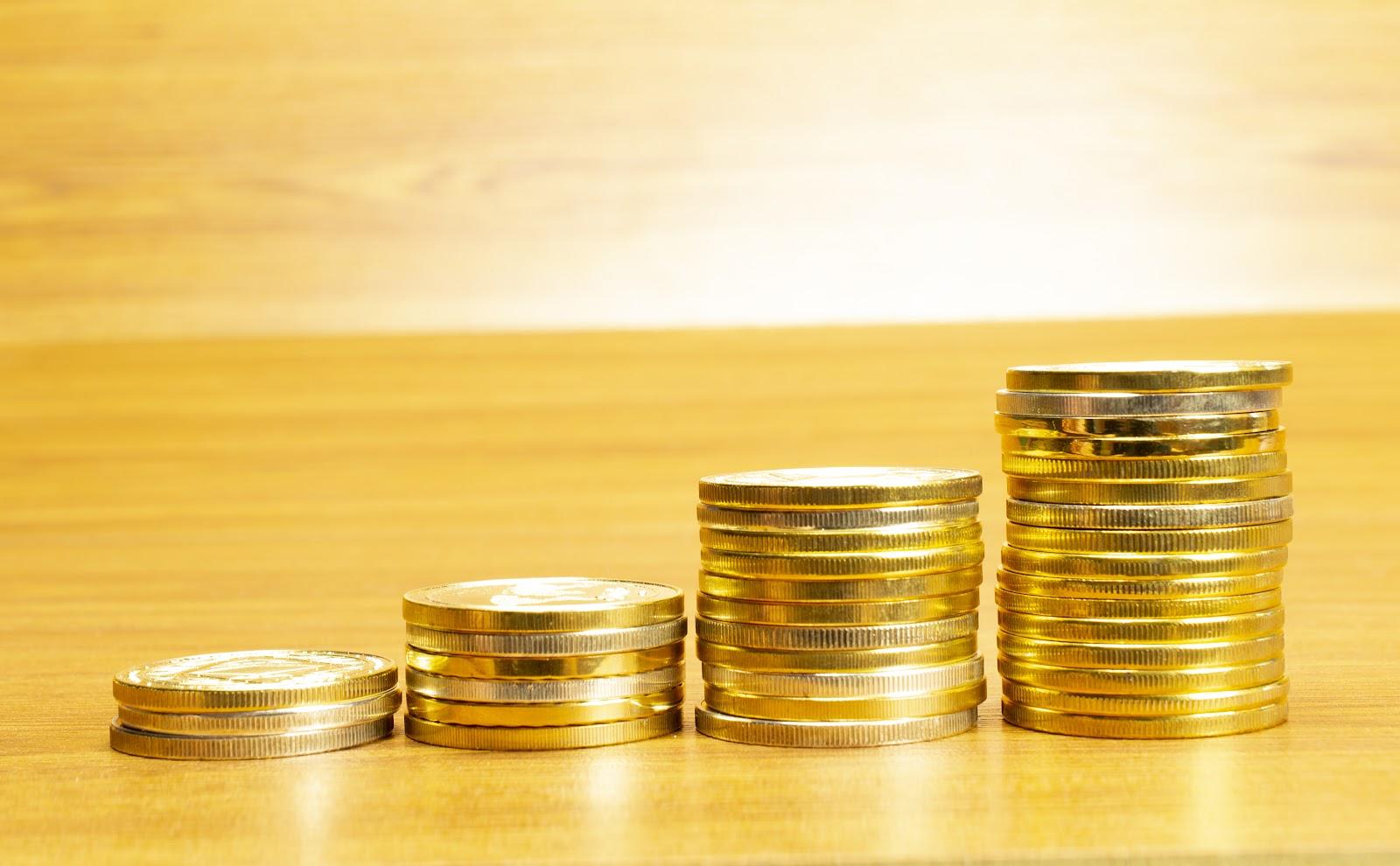 Visão lateral de uma mesa de madeira com uma pilha de moedas. O primeiro monte conta com 4 moedas, o segundo com 6, o terceiro com 11 e o quarto (e último) com 16 moedas. A imagem visa ilustrar a importância da contabilidade comercial.