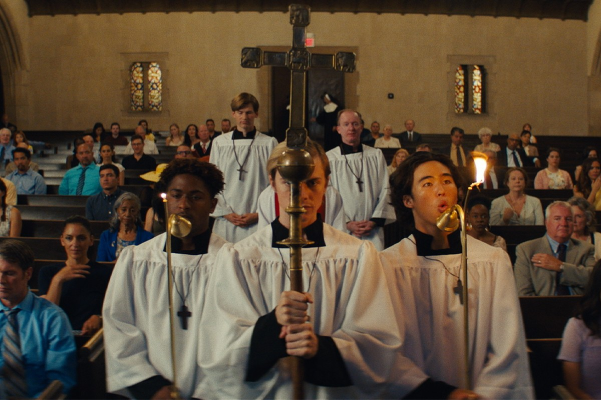 Film still depicting Adolf, Michael and Jay serving as altar boys during a church service. They're centered in the shot, with Michael in the middle as a cross-bearer carrying a processional cross as Jay and Adolf are seen at either side of him by bearing a lighted candle. Adolf, to the left, looks a mixture of bored and reserved while Michael looks very determined as he looks ahead of himself and holds the cross very tightly with both his hands. Jay is a bit more stressed as his candle has a way to big and bright flame that he's trying to control by blowing at it. Behind them are churchgoers of all ages seated, as well as other servers.