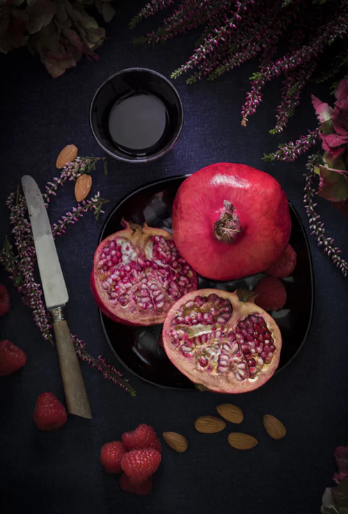 A whole and a sliced pomegranate on a black background.