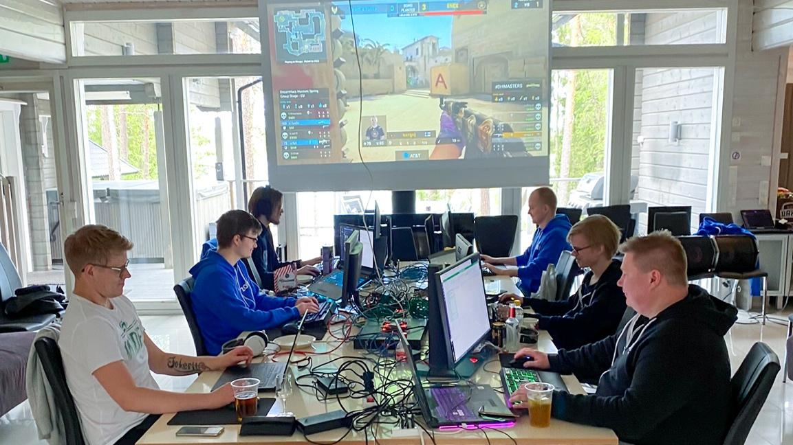 A group of people sitting at a table using a computer Description automatically generated