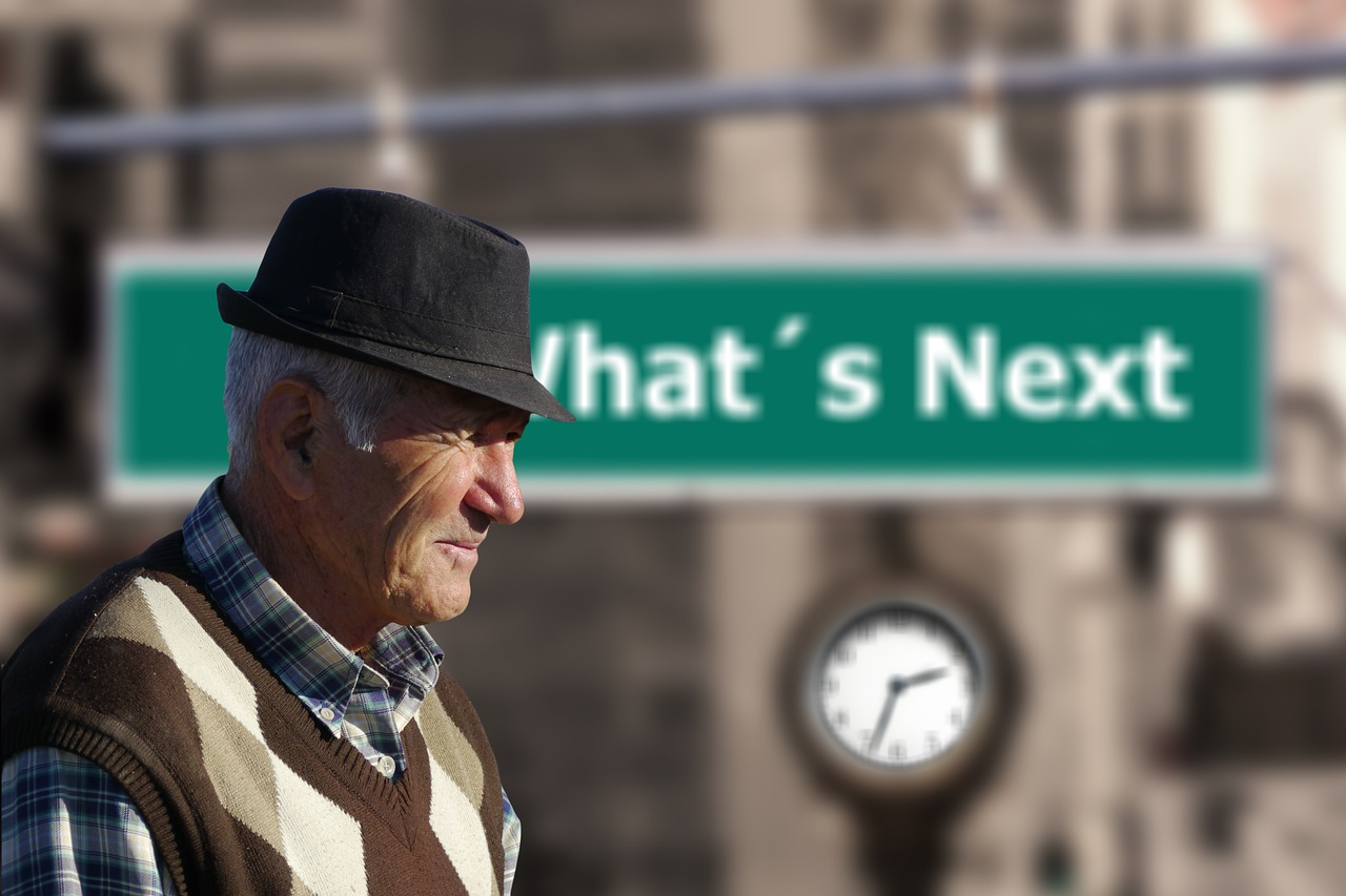 An elderly man walking past a clock and a sign saying what next.