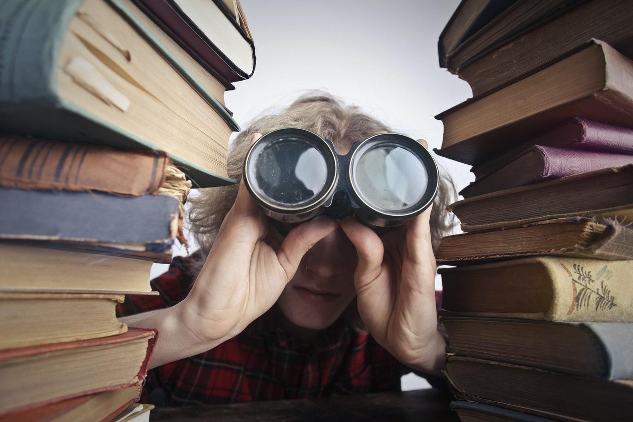Człowiek z lornetką pomiędzy dwoma stosami książek