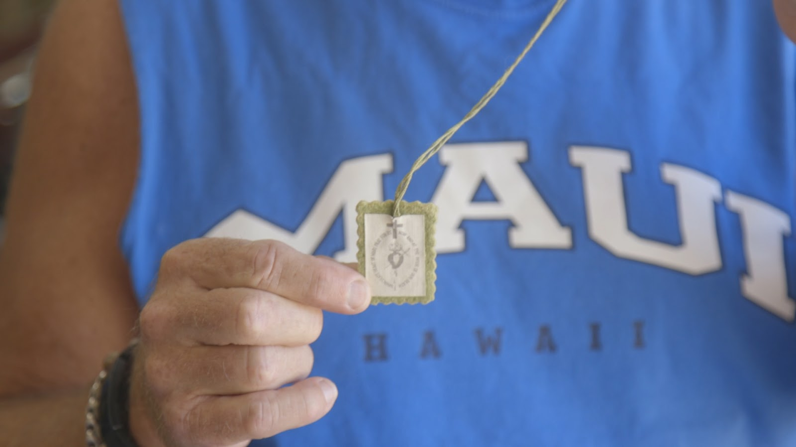 Tom McGuire holds the scapular he wore during college.