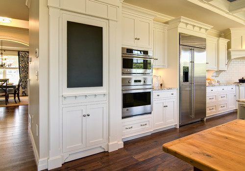 white hidden pantry door with white shaker cabinets and chalkboard