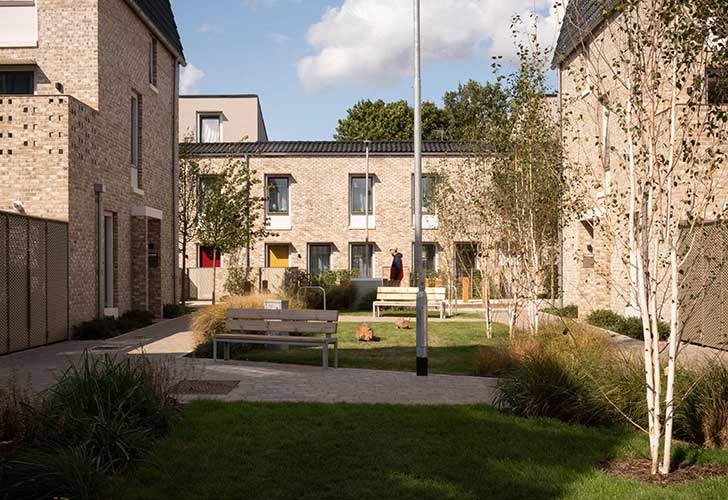 A bright sunny courtyard with benches and grass with pale stone houses around