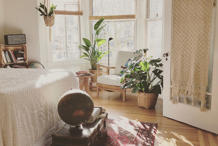 Fall bedroom decor using nature with many plants in the bedroom and natural colored bedding and wall paint.