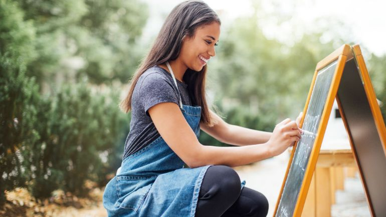 Woman writing on sandwich board with chalk