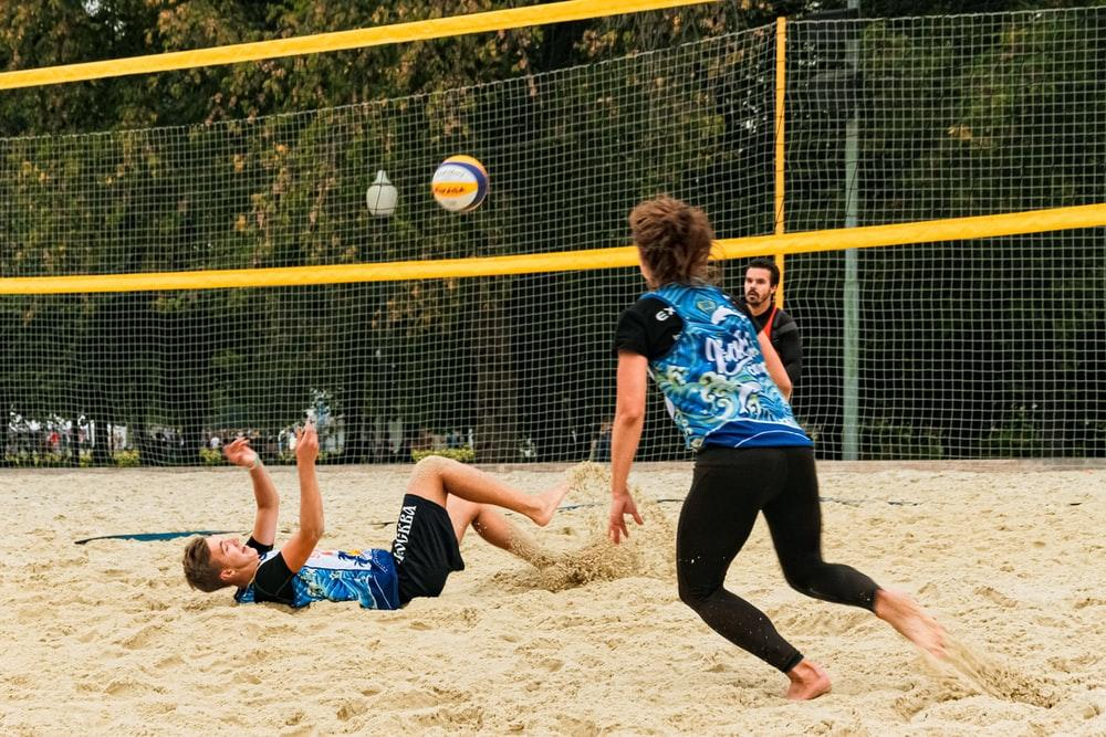 man and woman wearing blue and black jersey playing beach volleyball