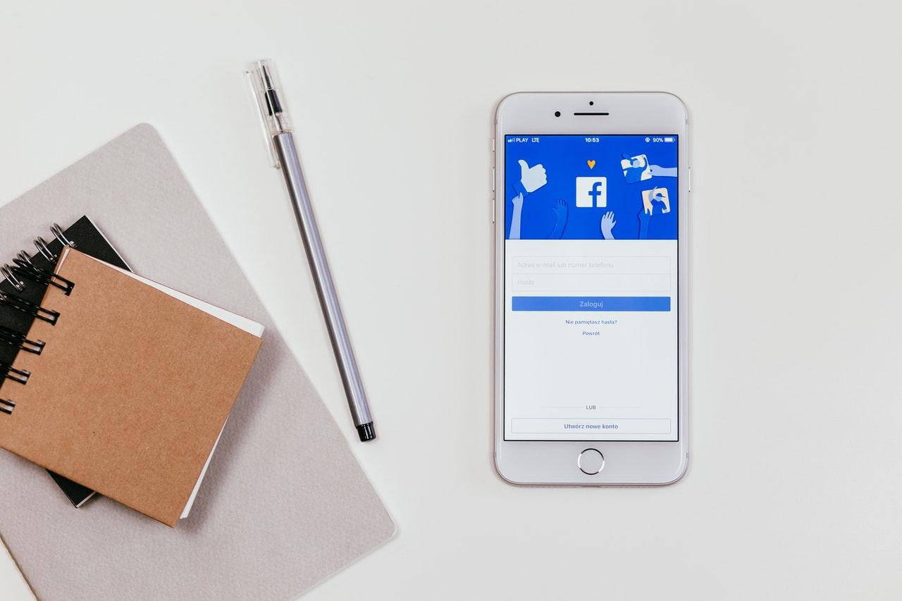 Aplikacja Facebook otwarta na telefonie komórkowym; długopisy i przybory biurowe na białym stole