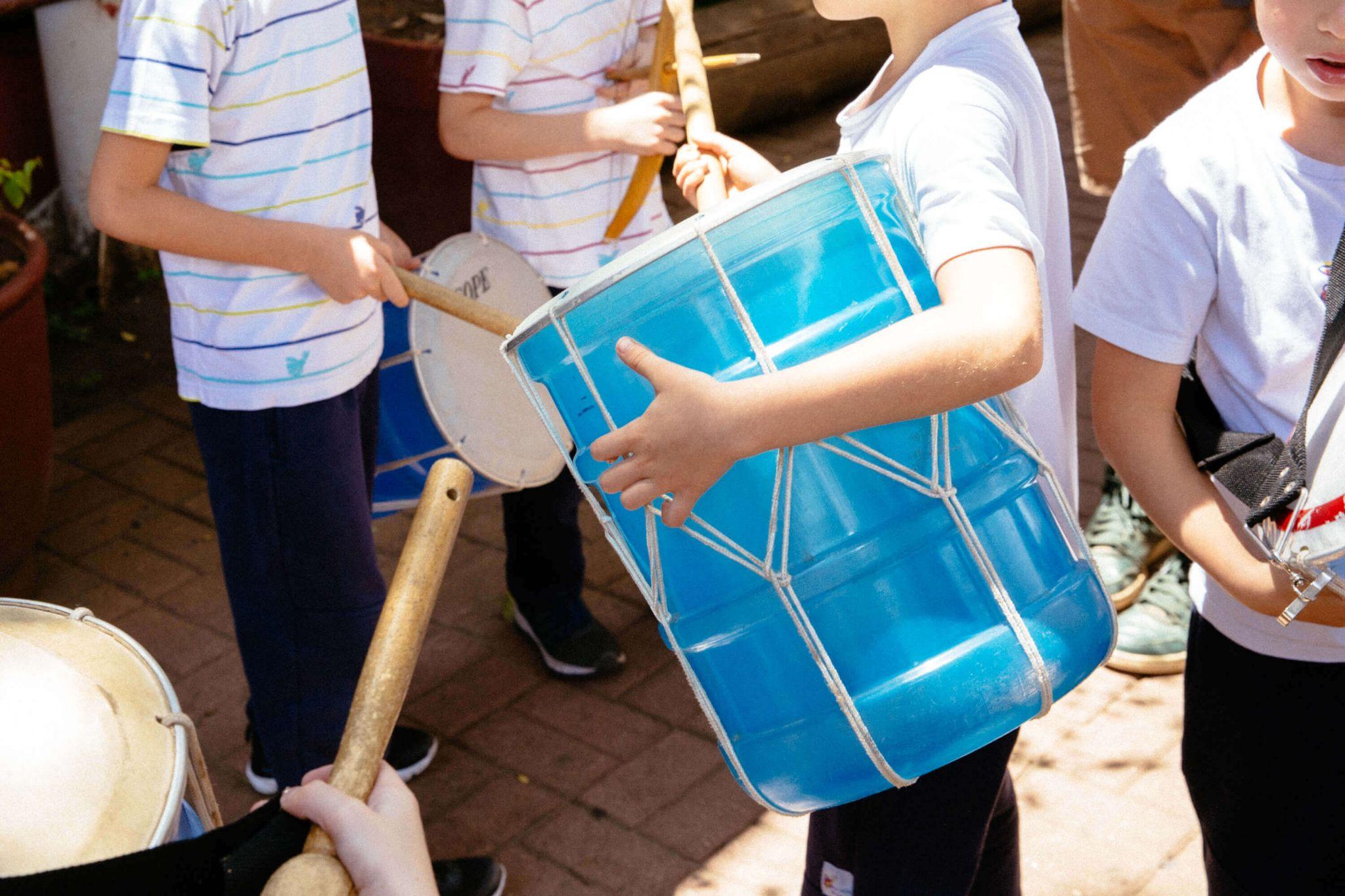 A imagem mostra um grupo de crianças com instrumentos musicais.
