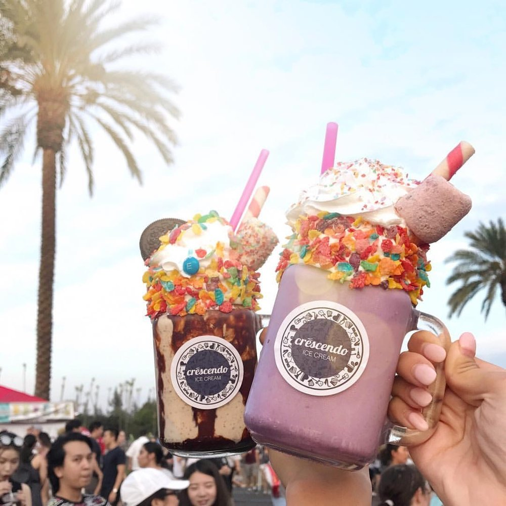 Two extravagant milkshakes held up in front of a palm tree at 626 Night Market