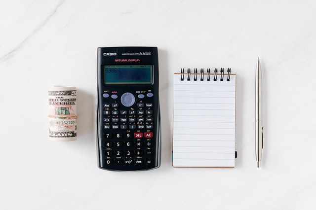 Cash, calculator, notepad and pen  side by side on a white surface.