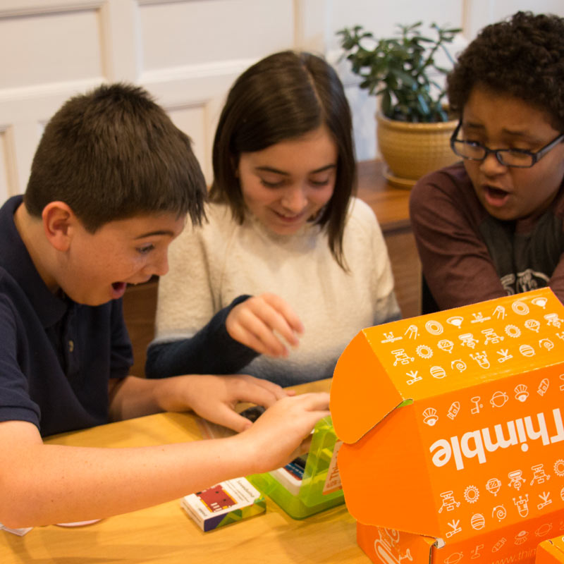Three children are smiling at a table as they open a Thimble Creator Kit together.