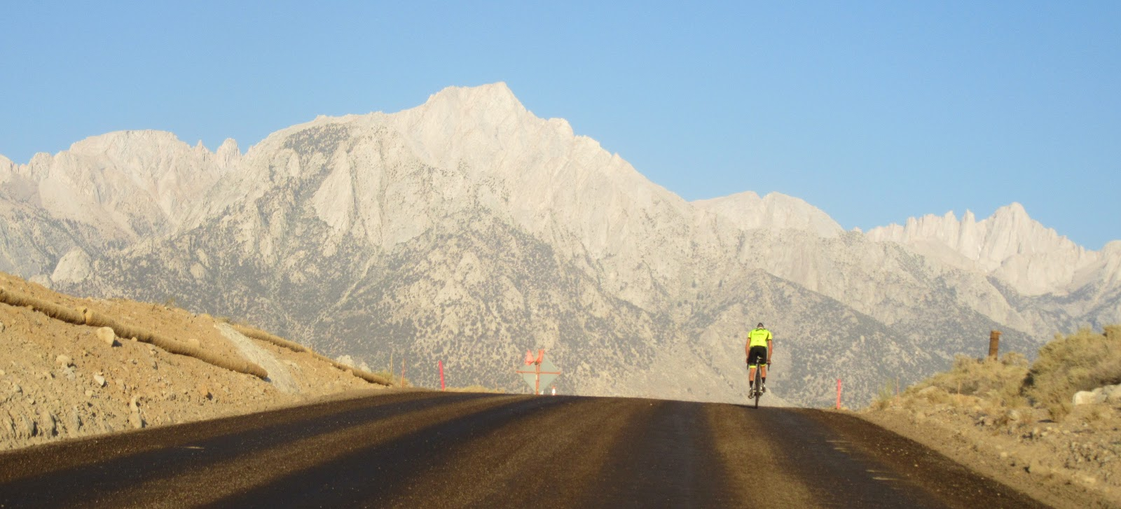 Cyclist on Whitney Portal Road with Mt. Whitney summit in background.