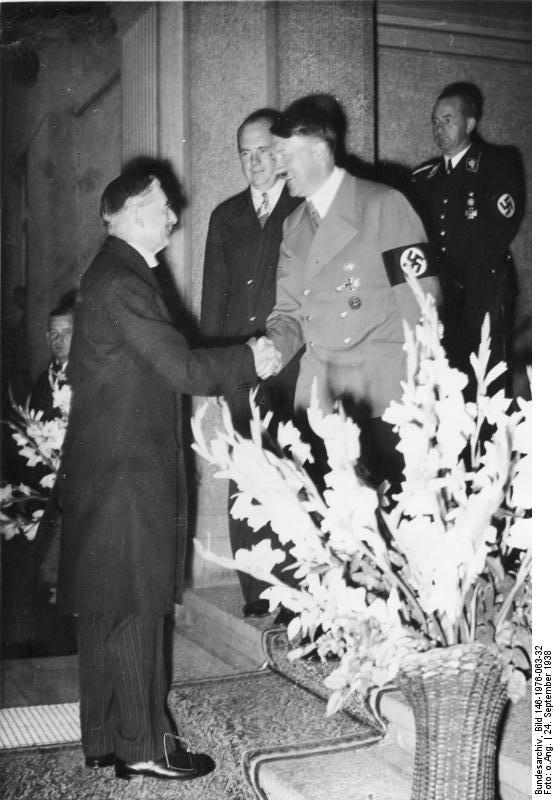 Prime Minister Chamberlain smiling and shaking hands with an equally cheerful Adolf Hitler.
