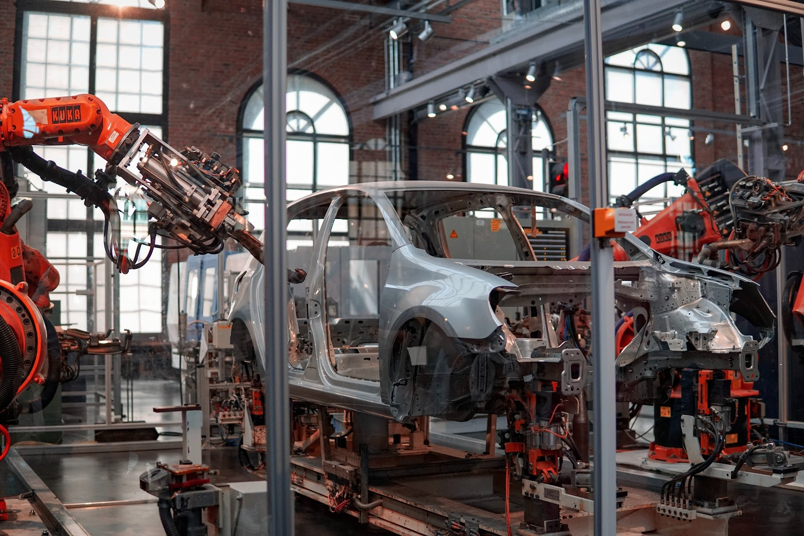 A car in a factory, being constructed by machines.