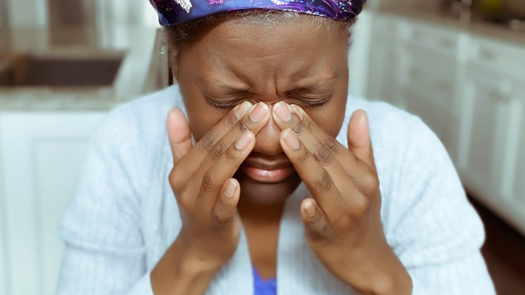 a woman holding the bridge of her nose as she has pain there from a migraine