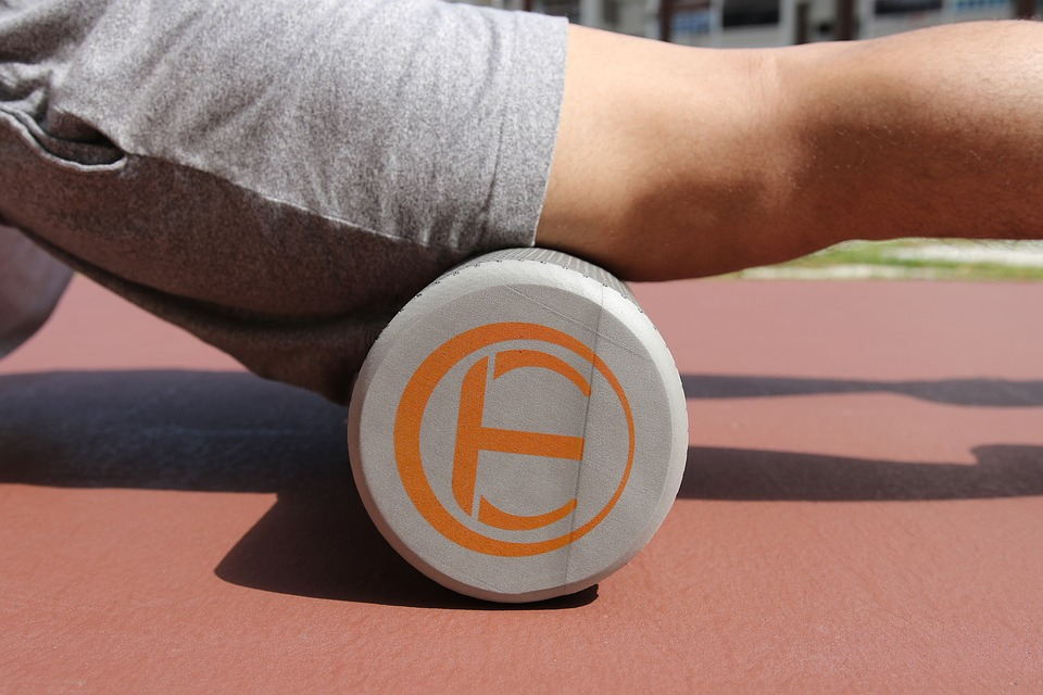 A person using a foam roller on their leg, which helps massage the muscles surrounding the sciatic nerve and relieve pain from sciatica.