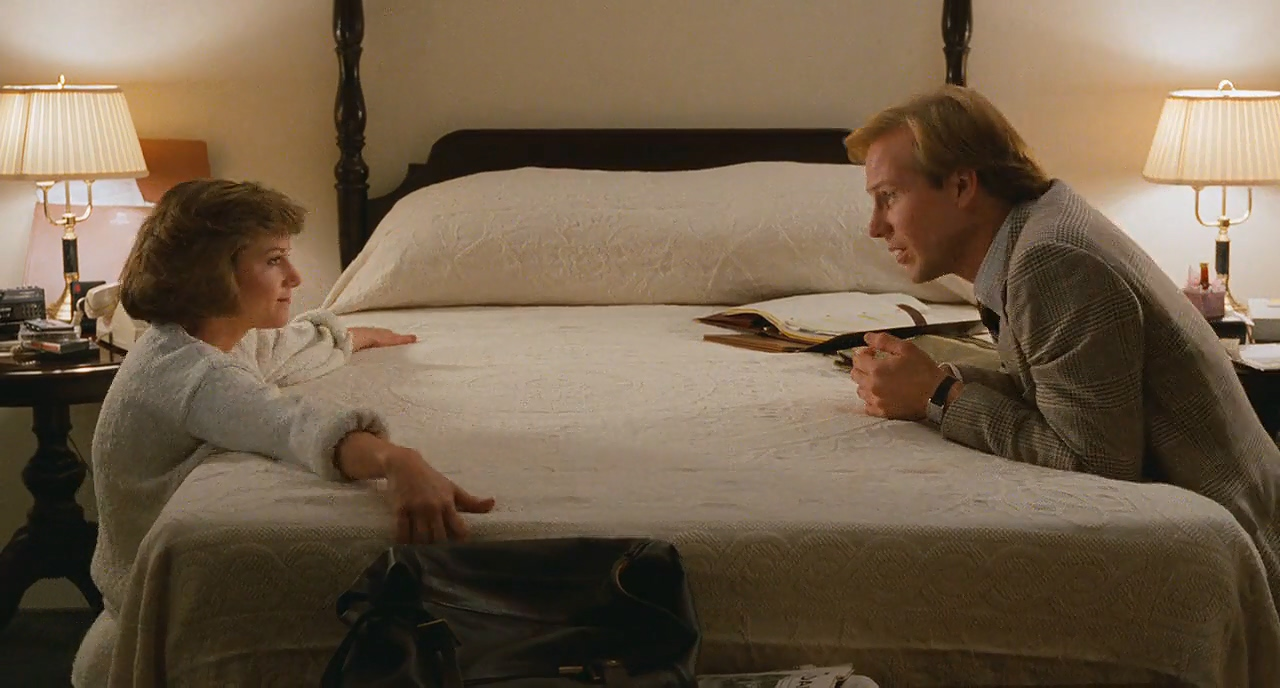 Holly Hunter as Jane Craig and William Hurt as Tom Grunick in Broadcast News. In the bedroom Jane, dressed in a white bath robe, is kneeling down beside the bed with her arms stretched out across the sheets. On the opposite side of the bed kneels Tom, in a grey suit. He leans across the bed towards Jane, speaking to her.
