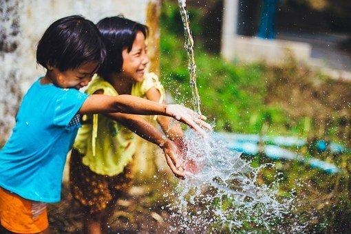 dzieci bawiące się na dworze z wodą