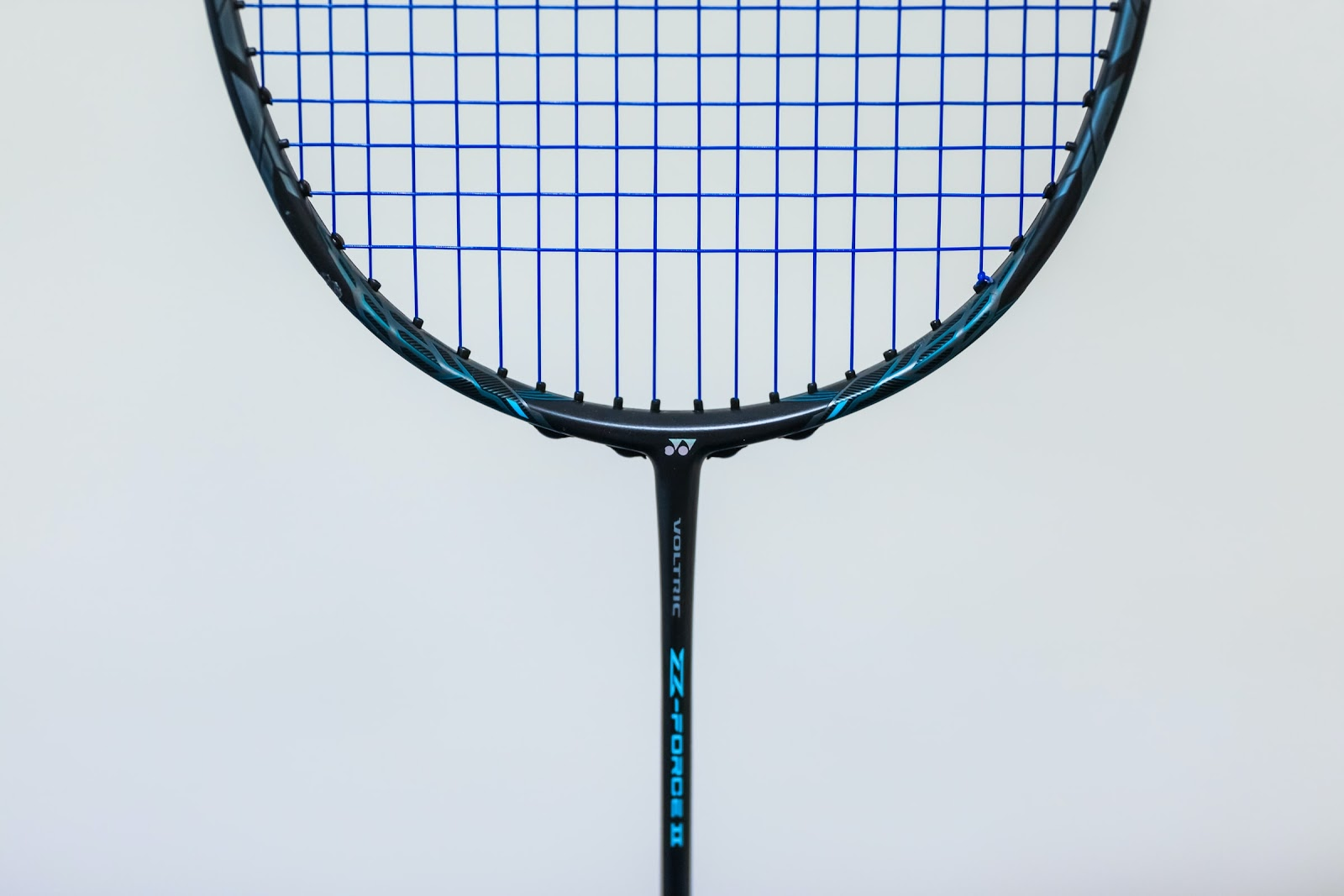A close up of the bottom of a badminton racket with blue strings.