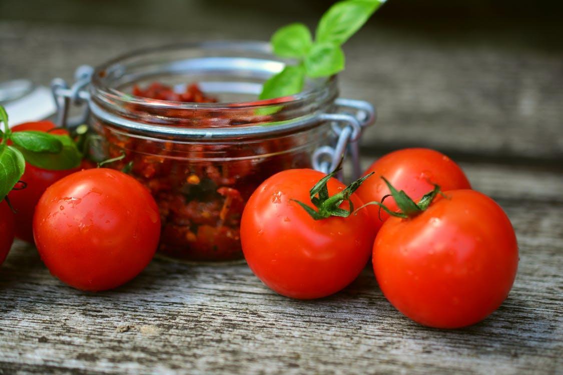 Red Tomatoes Near Glass Jar